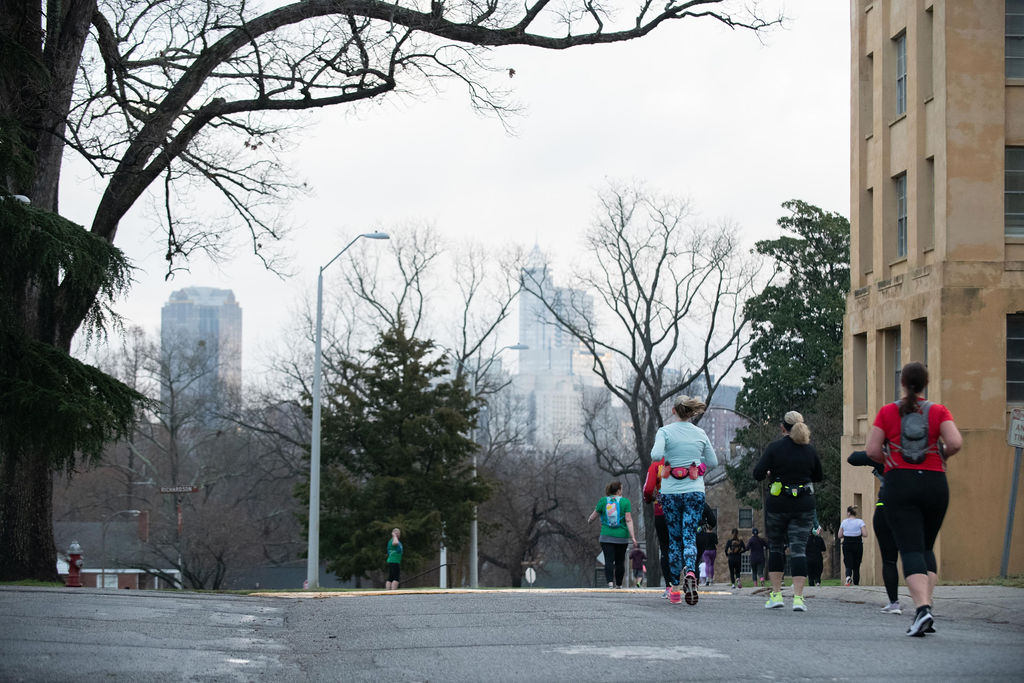 runners from behind with city skyline in background