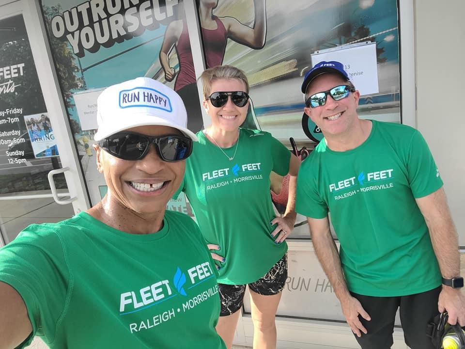 three people wearing matching green Fleet Feet Running Club t-shirts