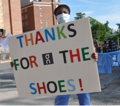 """woman in hospital attire holding """"thanks for the shoes"""" sign"""