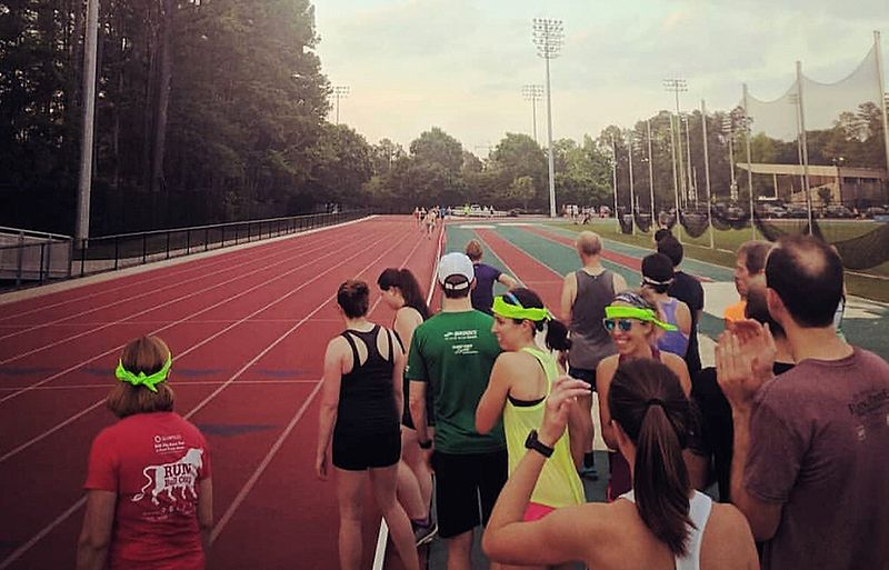 Runners on the side of a track cheering for each other