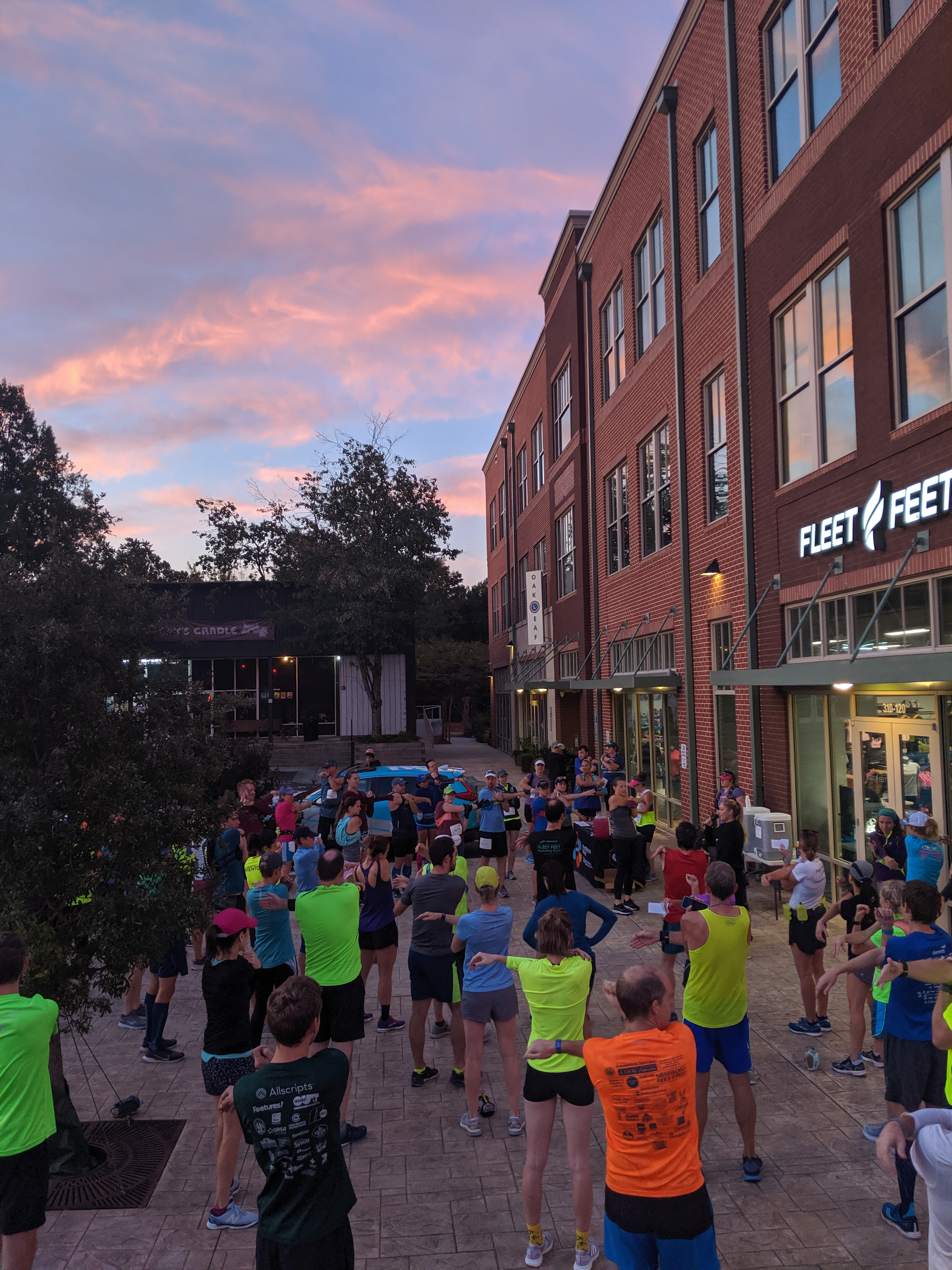 large group of runners outside fleet feet in carrboro under a sunrise