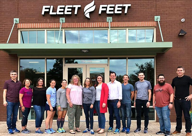 Employees stand in front of Fleet Feet store