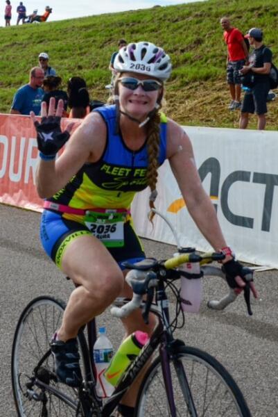 Laura biking at IRONMAN 70.3 Augusta and waving at the camera