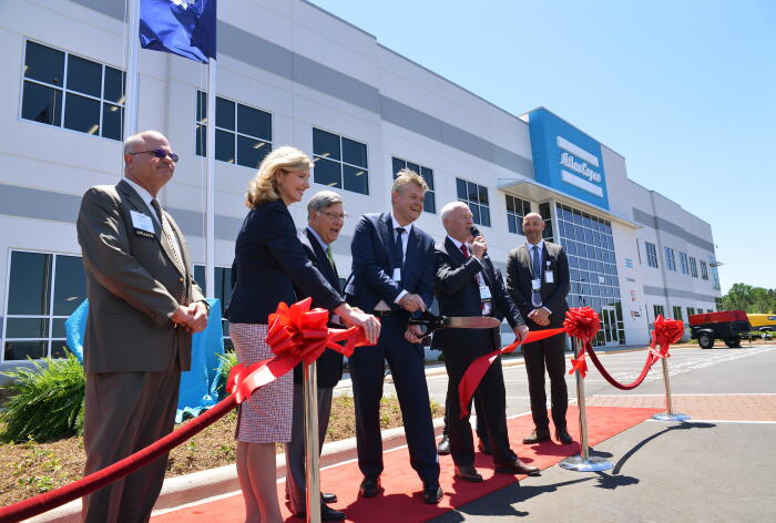 Atlas Copco executives along w/ local & state officials cut ribbon