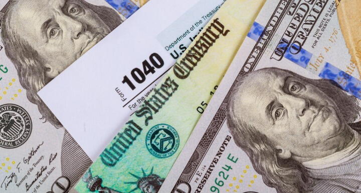 Tax Form 1040 beside one hundred dollar bills
