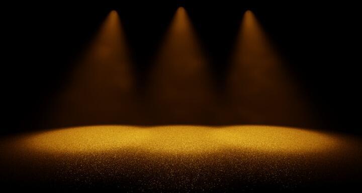 Three spotlights shining onto a stage