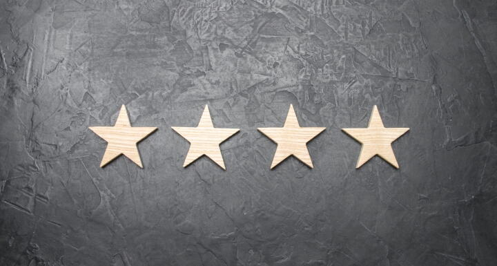 Four gold stars along a grey wall