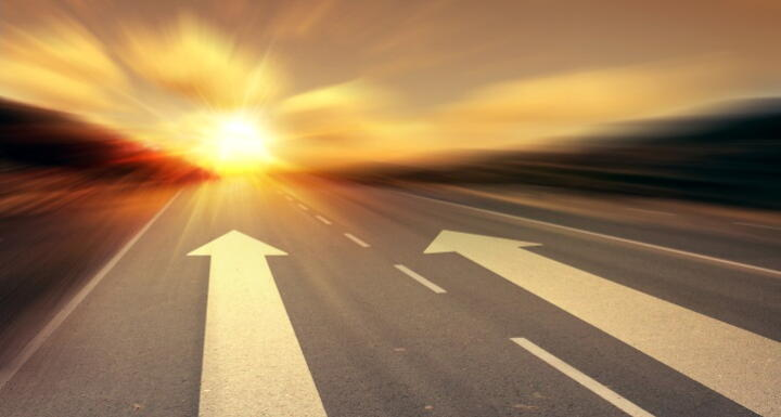Arrows on a road pointing towards the sunrise signifying growth and new direction