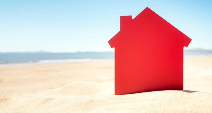 Red house cutout sticking out of sand on the beach