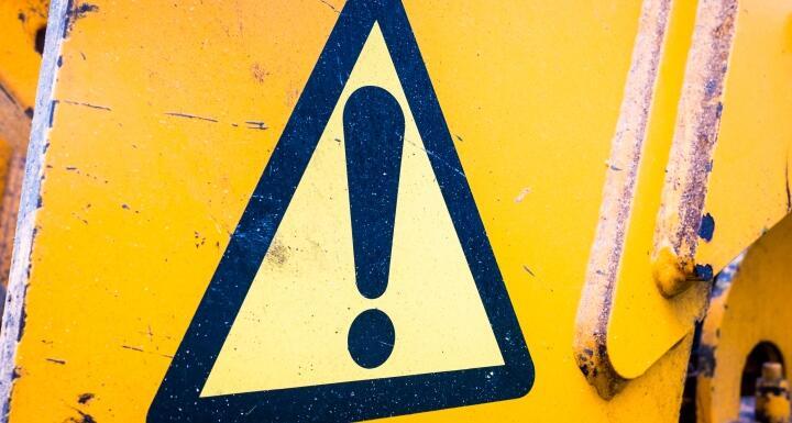 Yellow caution symbol on a dark yellow background