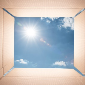 opened cardboard box with sky in background