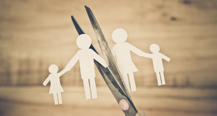 Small paper doll cutouts of a family being snipped in two pieces by kitchen scissors on a wooden background