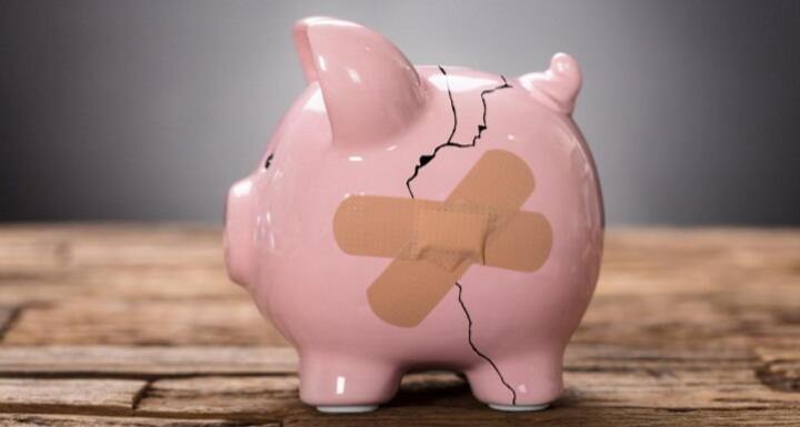 broken piggy bank with bandaid on crack
