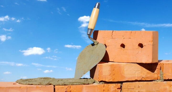 Rows of bricks and a trowel for bricklaying with a blue sky in the distance