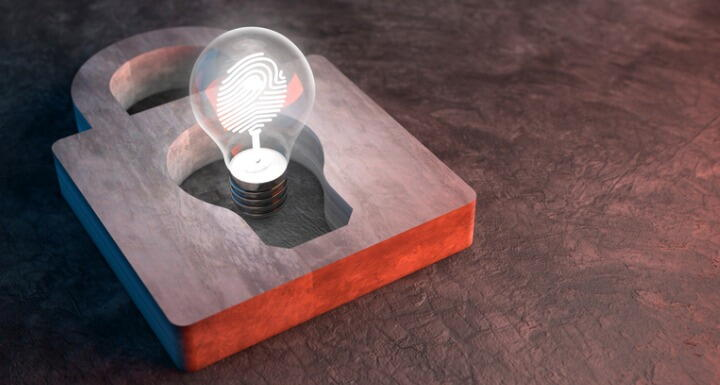 A lit lightbulb inside the keyhole of a padlock