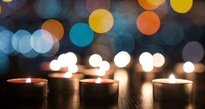 Several small lighted memorial candles on a darks background