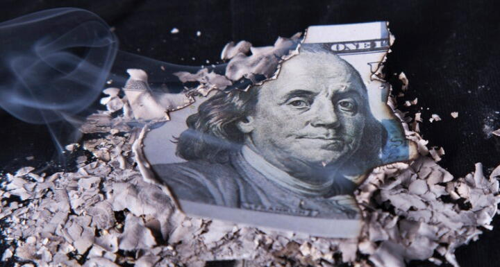 A one hundred dollar bill that has been burned around the edges