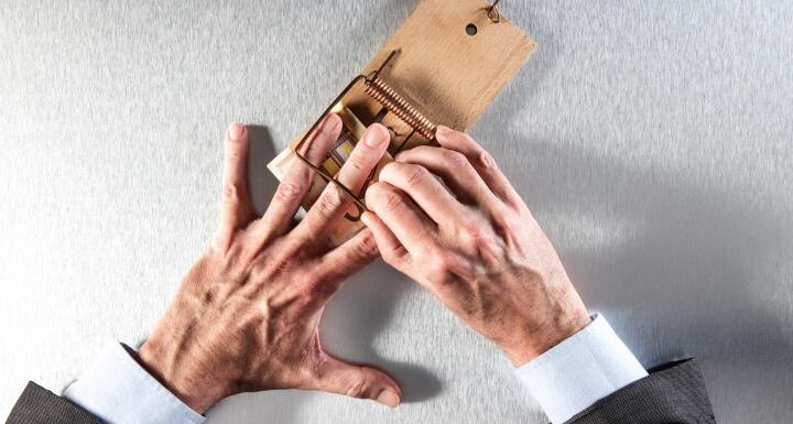 Businessman hand stuck in mouse trap