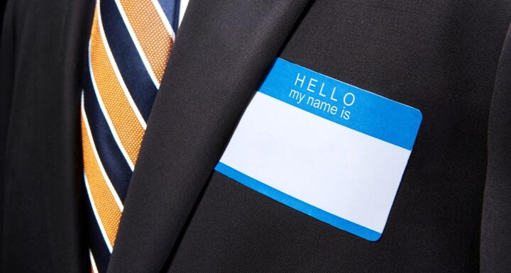 Businessman with blank, blue name tag sticker