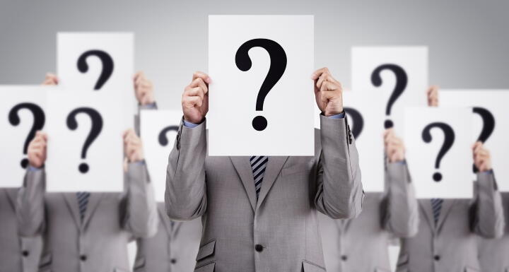 Businessmen holding signs with question marks over faces