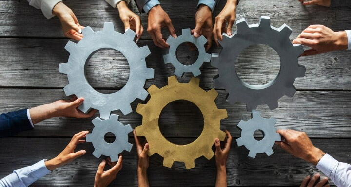 Hands of business people joining gold and silver gears