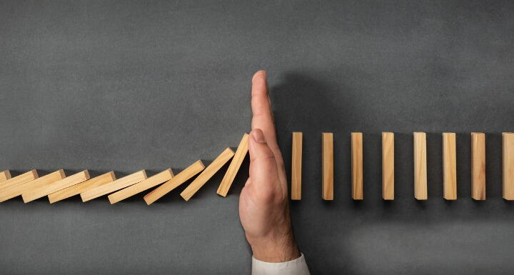 Businessman hand stopping falling dominoes
