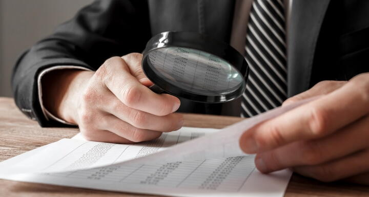 Man with Magnifying glass looking over contract