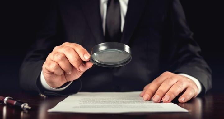 Man looking at a contract through a magnifying glass