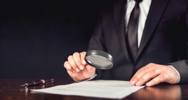 Businessman holding magnifying glass over document