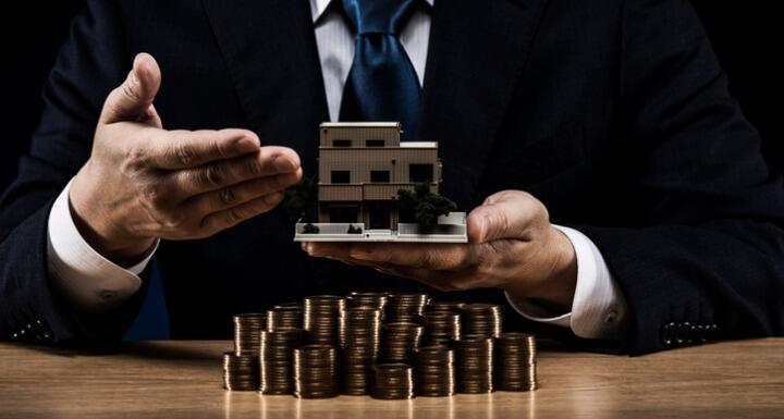 Businessman holding model building over stacks of coins