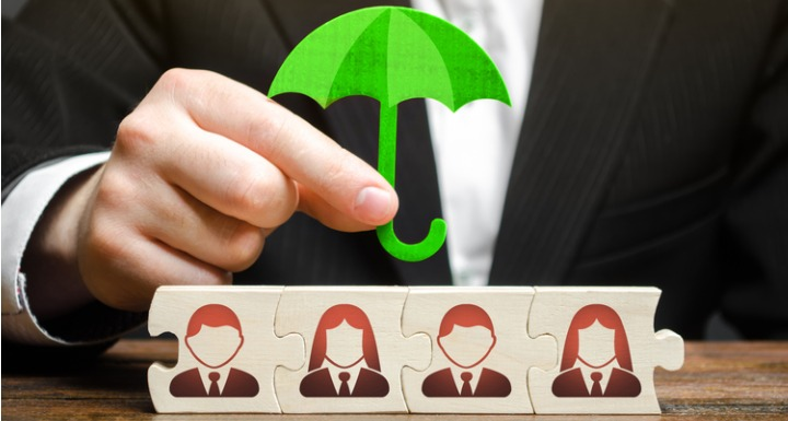 Businessman holding umbrella over puzzle pieces with business people avatars