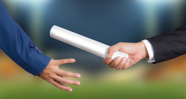 Close up shot of a businessman passing a silver baton to another businessman
