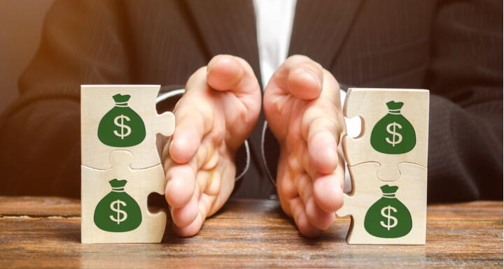 Businessman separating wooden puzzle pieces with images of money bags