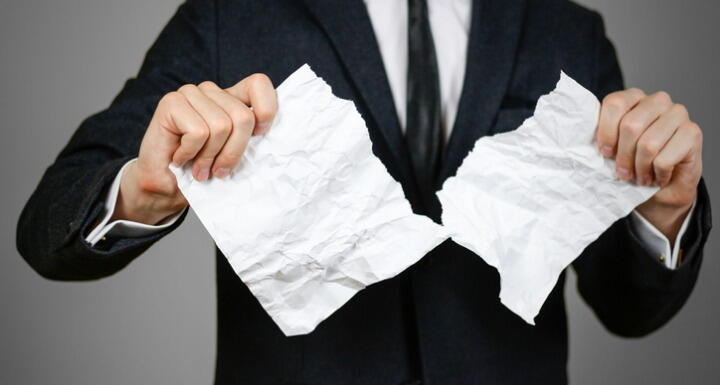A man in a suit tearing up a paper meant to show he is contesting a will