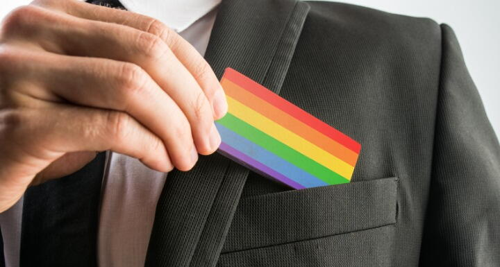 A man in a suit putting a rainbow business card in the outside chest pocket
