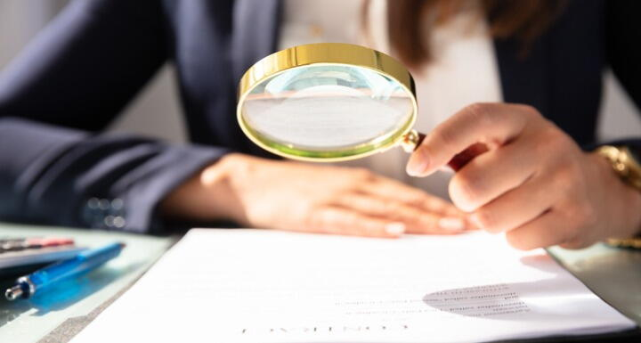 Businesswoman Looking At Contract Form Through Magnifying Glass