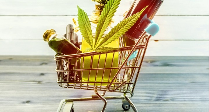 CBD goods including a leaf bar of soap and bottles of oil in a metal shopping cart