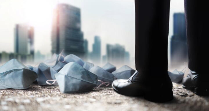 Many medical masks on the ground at business man's feet