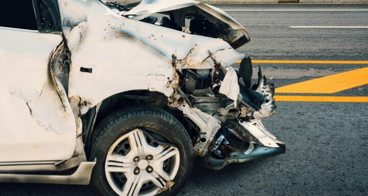 the front end of a white sedan with crash damage