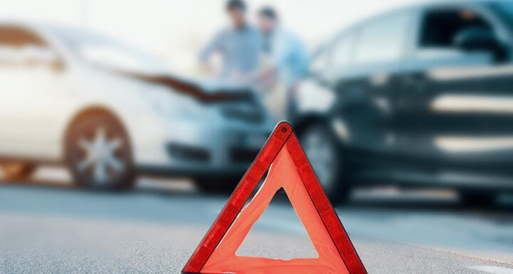 An orange caution pop up sign placed on the road with a two car accident in the background