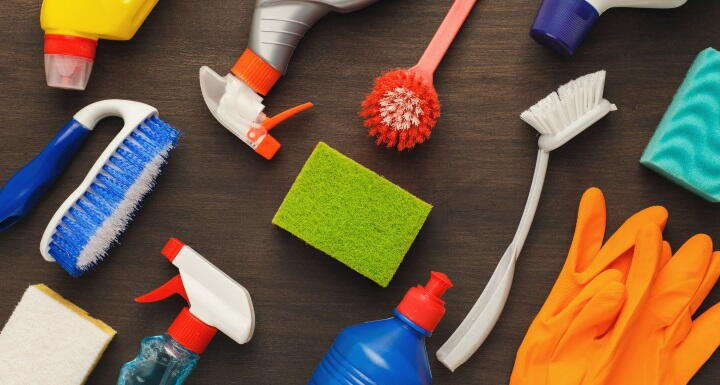 Multiple cleaning products laying on a brown table including several spray bottles and various cleaning brushes