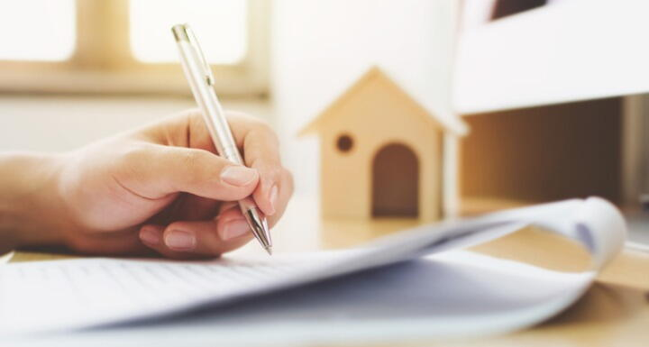 Close up hand of a man signing a signature document with an image of a house in the background