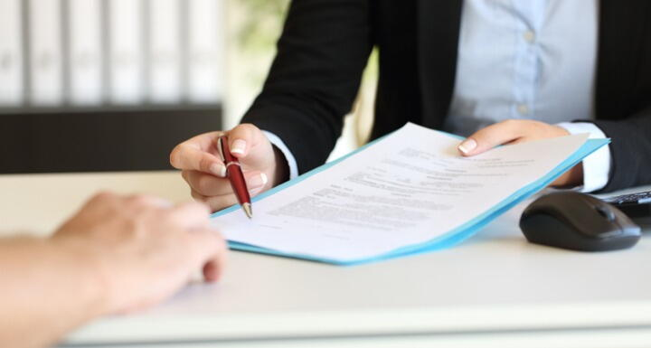 Close up of an executive hands holding a pen and indicating where to sign