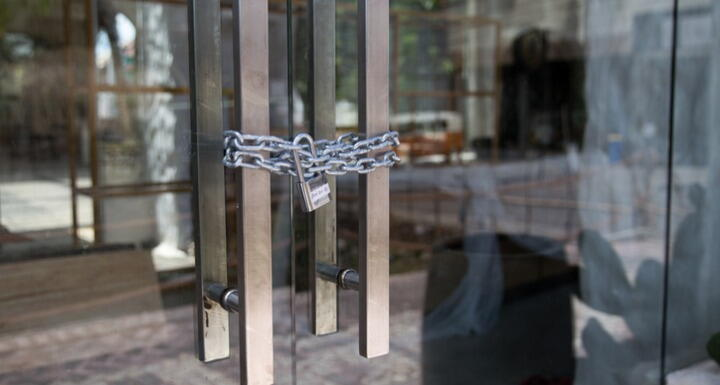 Closed glass door with metal chain and lock around handles