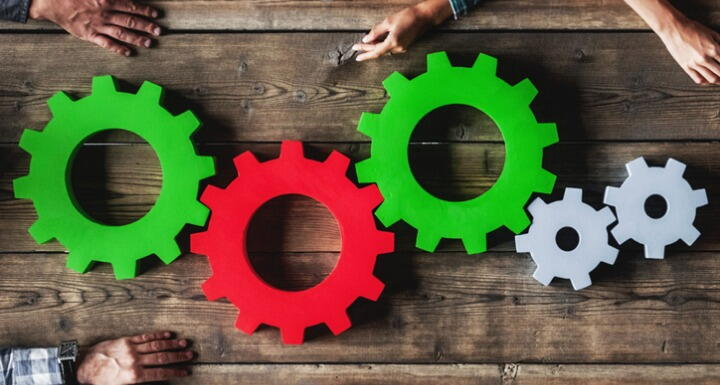 Green, red, and gray cogs and gears on wooden table