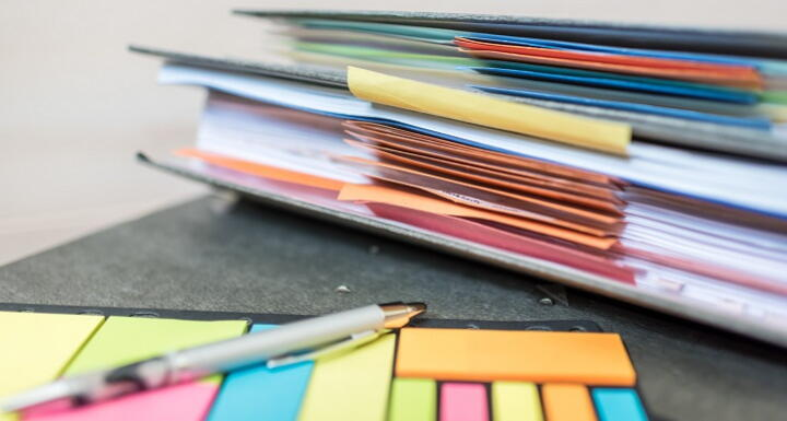Colorful post it notes and files on a desk
