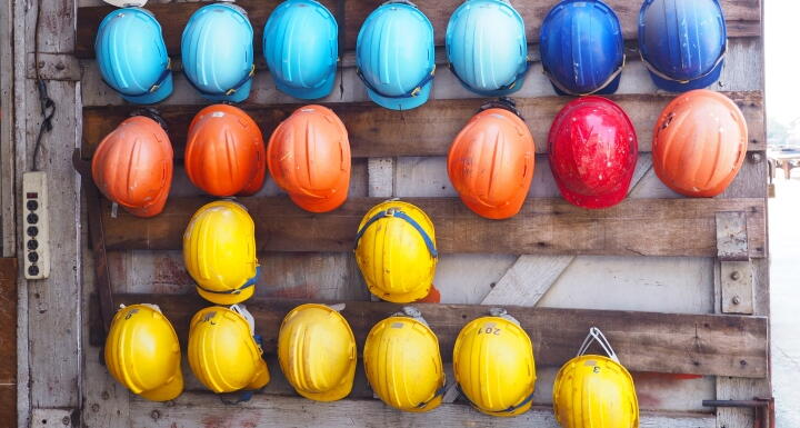 rows of colorful construction helmets hung on a wall