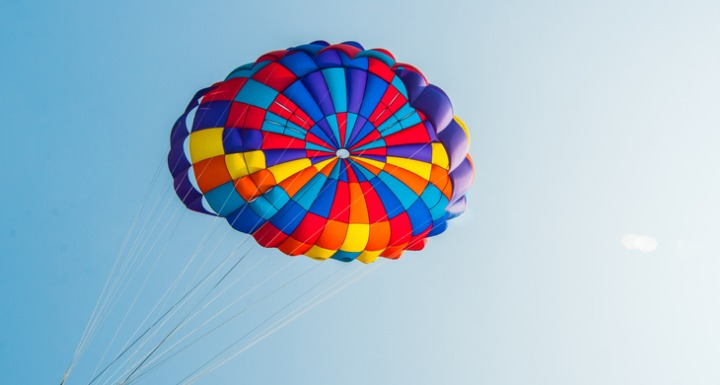 A colorful Rainbow striped parachute on a blue sky background