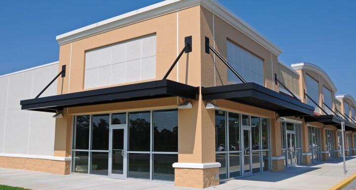 Tan and white commercial shopping building to illustrate commercial leases