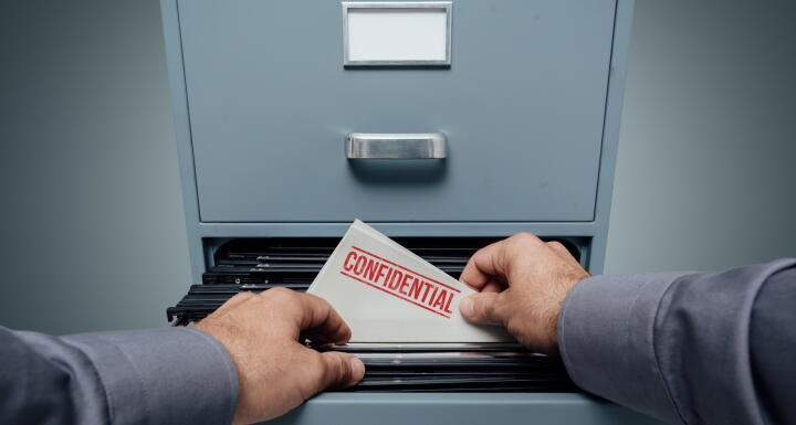 File labeled confidential being taken out of file cabinet